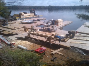 First day of boathouse construction on Lake Muskoka.  Barge provides easy access to building materials for the workers
